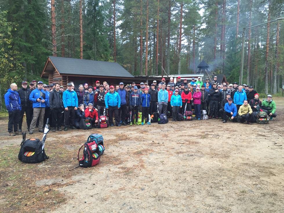 Savo Tour 2016 -pelaajat yhteiskuvassa lauantaiaamun pelaajakokouksessa Tervon Savelan frisbeegolfradalla (© Janne Mönkkönen).
